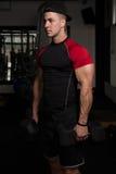 Spiermens die Bicepsen met Domoor uitoefenen Stock Foto's