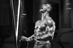 Spiermens die in gymnastiek uitwerken die oefening, sterke mannelijke torsoabs doen Stock Foto's