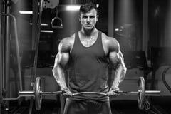 Spiermens die in gymnastiek uitwerken die oefeningen met barbell doen bij bicepsen Stock Foto's