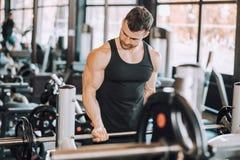 Spiermens die in gymnastiek uitwerken die oefeningen met barbell doen bij bicepsen stock foto