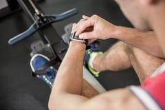Spiermens op het roeien machine die slim horloge met behulp van royalty-vrije stock afbeeldingen