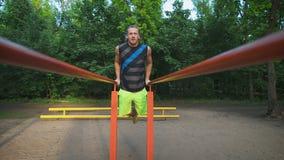 Spiermens tijdens zijn training in park Onderdompelingen, oefeningsborst en triceps stock footage