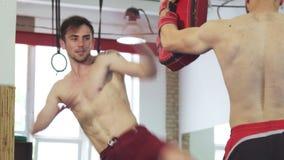 Spierschopbokser die shirtless het doen hoge schoppen bij het schoppen van stootkussens uitwerken stock video