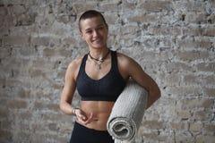 Spiervrouw die yoga doen binnen stock afbeelding