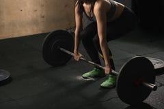 Spiervrouw in een gymnastiek die zwaargewicht oefeningen met barbell doen stock afbeelding