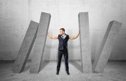 Spierzakenman volledig-hoogte concrete vier kolommen houden die vallend op hem Stock Afbeelding