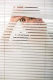 Spies. The woman looks through jalousie Royalty Free Stock Image