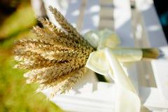 Spighette di grano in un mazzo che mette sull'erba Fotografia Stock Libera da Diritti