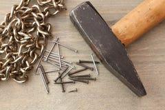 Spijkers en hamer op houten lijst stock fotografie