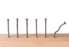 Spijkers in houten plank. stock afbeeldingen