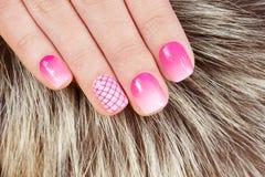 Spijkers met manicure met roze nagellak op bontachtergrond die wordt behandeld Stock Afbeelding