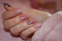 Spijkers met roze lak met een patroon van sakura worden behandeld die en maar Stock Afbeelding