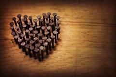 Spijkers op een raad in de vorm van hart stock foto