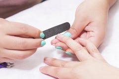 Spijkersmanicure met dossier Vrouwen mooie nagelverzorging na het vullen stock afbeelding