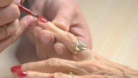 Spijkerspecialist die rood poetsmiddel toepast stock footage