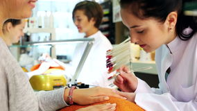 Spijkertechnici die manicureprocedure in schoonheidssalon uitvoeren stock videobeelden