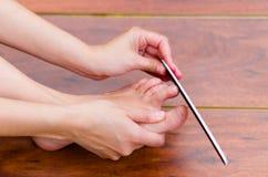 Spikar av fot får mappen, når att ha klippt, pedikyrmoment Royaltyfria Bilder