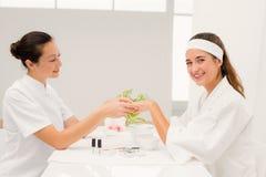 Spikar den härliga kvinnan för ståenden med kosmetologen som att applicera spikar fernissa till kvinnliga klienter Fotografering för Bildbyråer