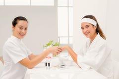 Spikar den härliga kvinnan för ståenden med kosmetologen som att applicera spikar fernissa till kvinnliga klienter Royaltyfria Foton