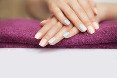 Spikar i brunnsorten härlig manicure Kosmetiska tillvägagångssätt med händer och spikar Ligga på ett gevär Begreppet av skönhet o arkivfoton