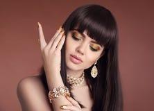 Spikar manikyr Stående för skönhetflickabrunett Guld- je för mode royaltyfria bilder