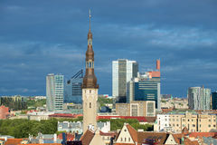 A spike of a medieval town hall close up against the background of the modern city, Tallinn Royalty Free Stock Photos