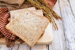 Spike and whole wheat bread on white wooden table Royalty Free Stock Photography