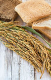Spike and whole wheat bread on white wooden table Royalty Free Stock Photos