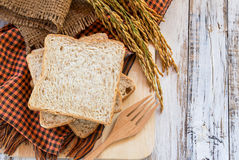 Spike and whole wheat bread on white wooden table Stock Image