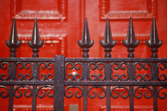 Spike wrought iron fence in front of red door at boarding school, NY Royalty Free Stock Photos