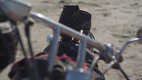 Spiked παπούτσια με τα υψηλά τακούνια και το μαύρο και κόκκινο φόρεμα που βρίσκονται στην κινηματογράφηση σε πρώτο πλάνο μοτοσικλ απόθεμα βίντεο