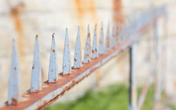 Spiked fence, rusty old spikes Royalty Free Stock Photos