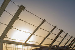 Spiked wire on the fence in the prison during the sunset time Stock Photo