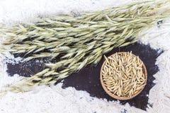 Spikelets των βρωμών και του ξύλινου κύπελλου με το σιτάρι στο αλεύρι Τοπ όψη στοκ εικόνες με δικαίωμα ελεύθερης χρήσης