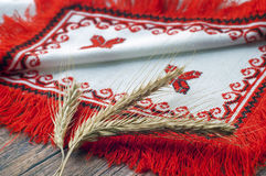 Spikelets of wheat lie on towel. Three spikelets of wheat lie on embroidered Ukrainian towel Stock Images