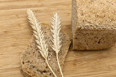 Spikelets of wheat and rye bread. On kitchen board Stock Images