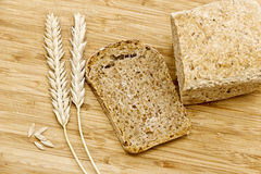 Spikelets of wheat and rye bread. On kitchen board Stock Image