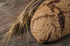 Spikeletsna och det bakade brödet på en träbakgrund Arkivbild