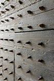 Spikes Door. Close-up shot of a dark, ancient, heavy, wooden door with metal spikes. Croatia Royalty Free Stock Image