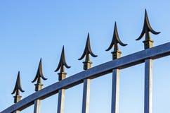 Spikes on Galvanised Gate Against Blue Sky. Underview of spikes on galvanised gate against blue sy stock image