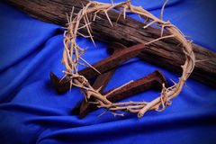 Spikes, Thorns & Beam on Blue. A woven crown of thorns, rusty spikes with a rustic timber on a blue woven cloth. Used in the Crucifixion of Jesus in Stock Photos