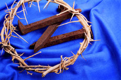Spikes and Thorns on Blue. A woven crown of thorns, rusty spikes on a blue woven cloth. Used in the Crucifixion of Jesus. Easter symbols. Copy Space Stock Image