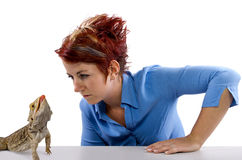Spikey. Haired girl staring at  bearded dragon reptile Royalty Free Stock Images