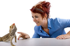 Spikey. Haired girl staring at  bearded dragon reptile Royalty Free Stock Photo