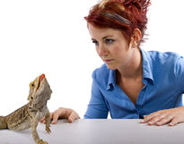 Spikey. Haired girl staring at  bearded dragon reptile Stock Photo