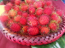Spiky Lychee Fruits in a Red Basket Stock Photo