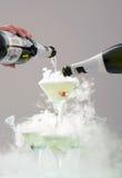 Spill av champagne i festliga exponeringsglas Arkivfoton