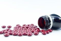Spill för preventivpillerflaska, röda preventivpillerar av vitaminet och medicin på vit Arkivbild