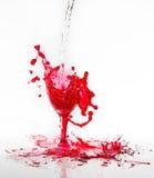 Spill för rött vatten från ett brutet vinexponeringsglas på en vit bakgrund Fotografering för Bildbyråer