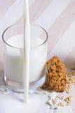 Spill mjölkar nära exponeringsglas mjölkar av med havremjölkakan Fotografering för Bildbyråer